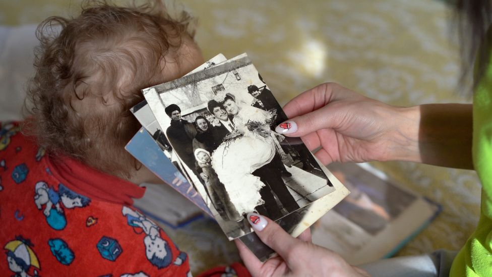 Hanna Kostseva looks at a photograph of her parents' wedding