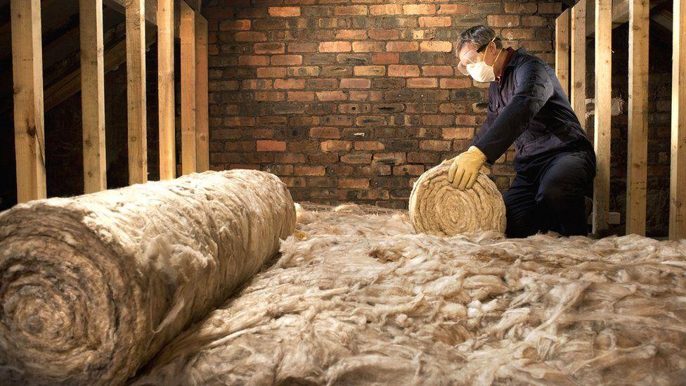 Man laying loft insulation