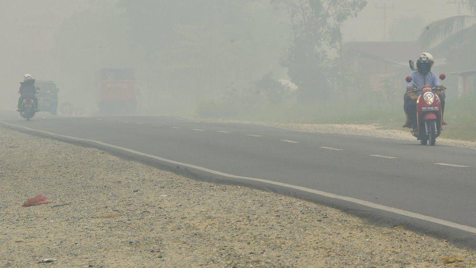 Motorists drive down a street as haze shrouds the area in Pekanbaru, Riau province on 14 September 2015.