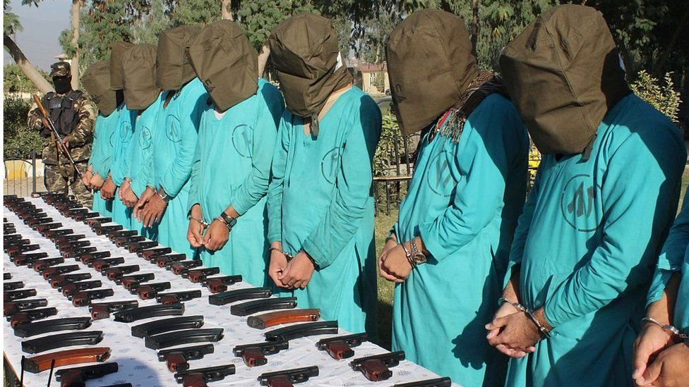Hooded alleged members of IS and the Taliban, standing in front of a table of guns in Jalalabad eastern Afghanistan on 6 December 2016.