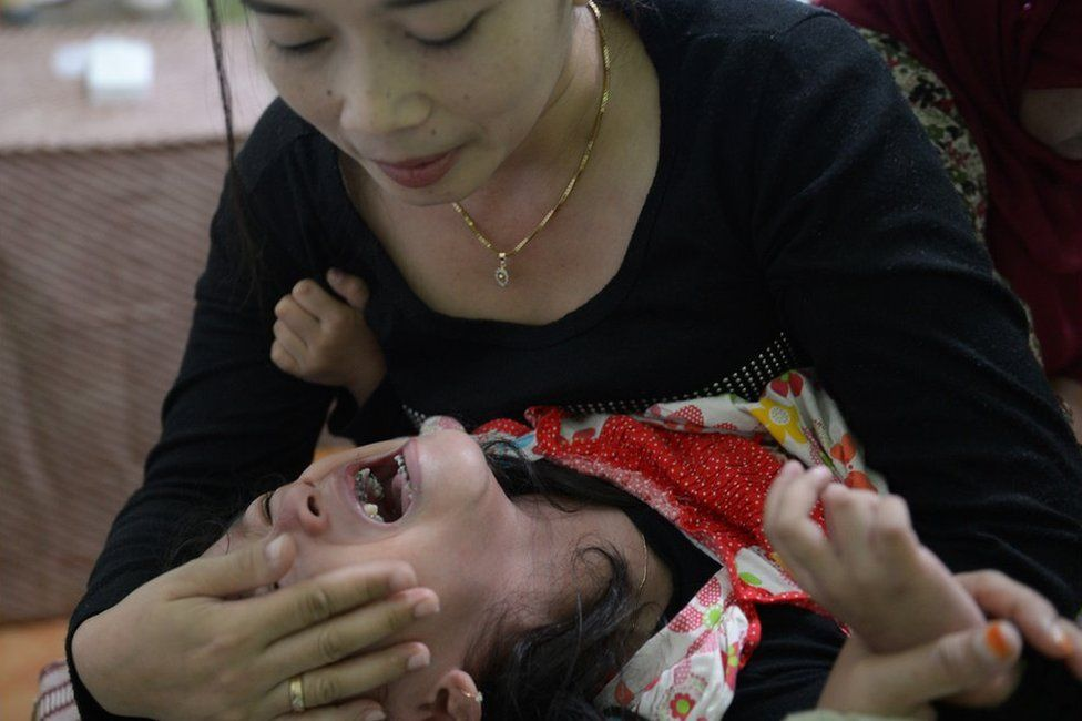 This picture taken on February 10, 2013 shows Indonesian mother Desi (top) trying to calm her four and half year-old daughter Kania as doctors (back R) perform her circumcision in Bandung