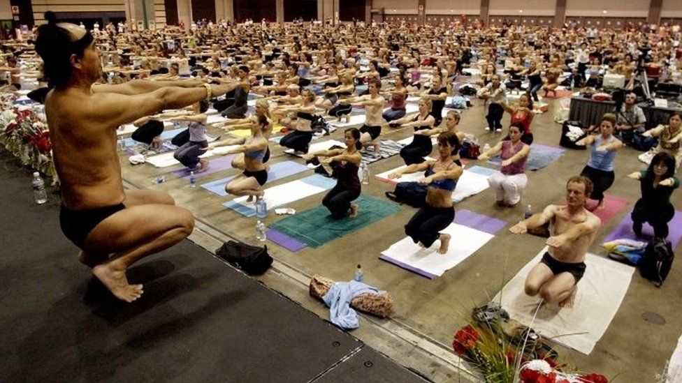 In this Sept. 27, 2003, file photo, Bikram Choudhury, front, founder of the Yoga College of India and creator and producer of Yoga Expo 2003, leads what organizers hope will be the world's largest yoga class at the Expo at the Los Angeles Convention Centre.