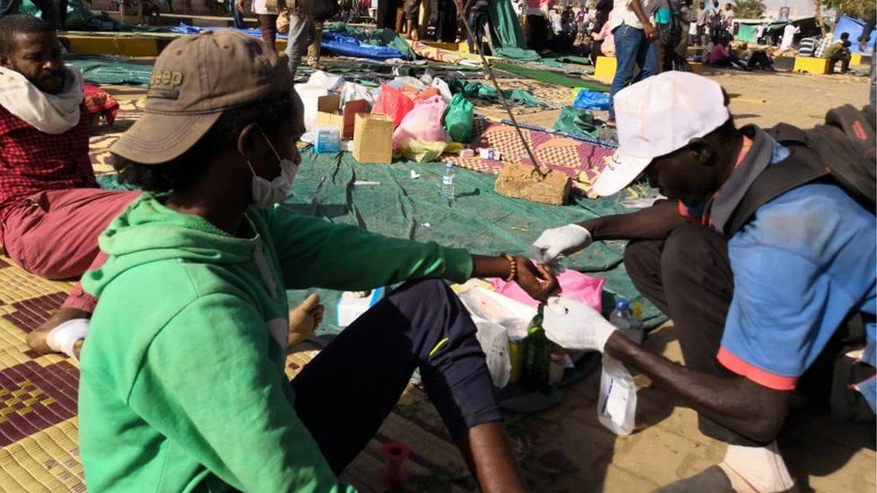 A Sudanese protester tends to the wounds of a fellow demonstrator during a rally in front of the military headquarters in the capital Khartoum on April 9, 2019.