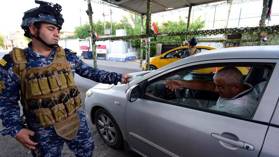Iraqi police officer checks the identity papers of a driver in Baghdad's Karrada district (12 May 2019)