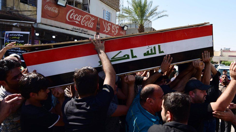 Iraqis carry the coffin of a protester allegedly killed in clashes with security forces in Baghdad (5 October 2019)