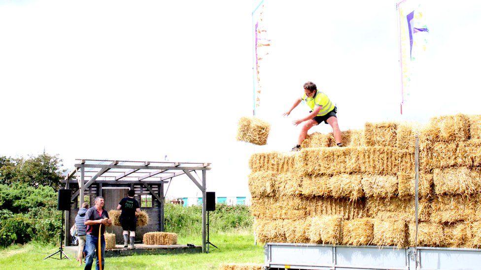 Seddau o wellt ar gyfer llwyfan y Llannerch // Offloading bales of hay that will become seats