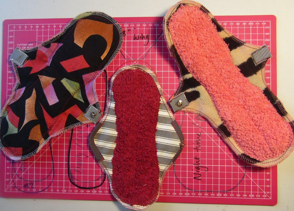 Three reusable menstrual pads laid out on a cutting mat