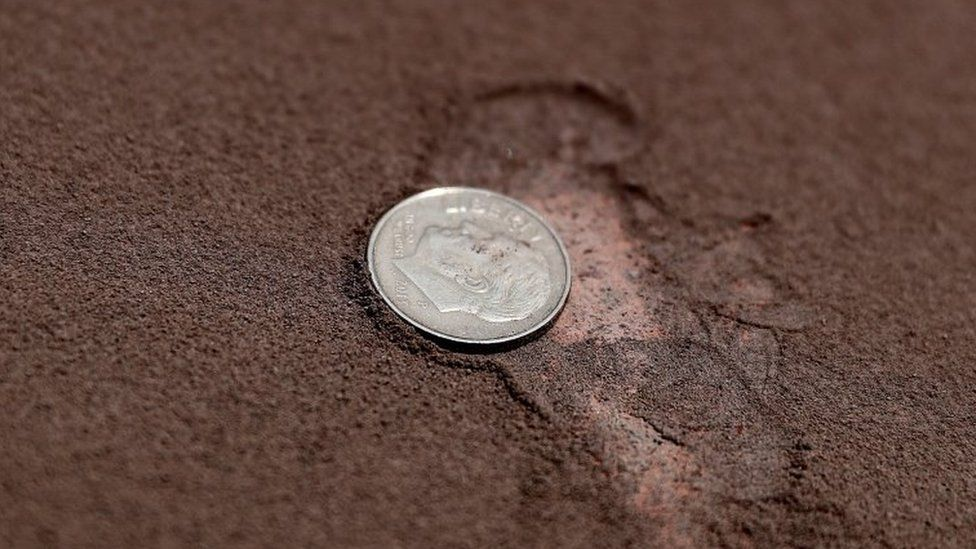View of a coin next to the ash from the Sangay volcano on a street in Alausi, in the province of Chimborazo, Ecuador, 20 September 2020.