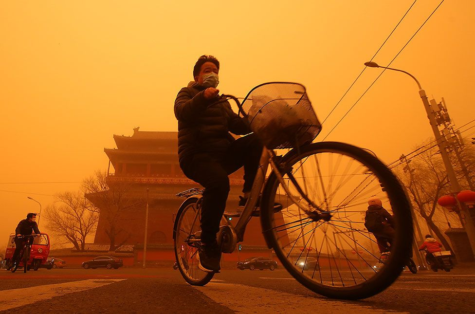 A cyclist passes a temple whilst surrounded by a thick sandstorm