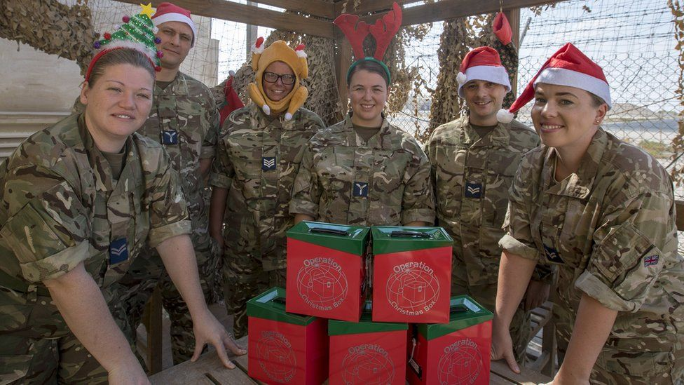Six members of the armed forces wearing Christmas-themed headwear