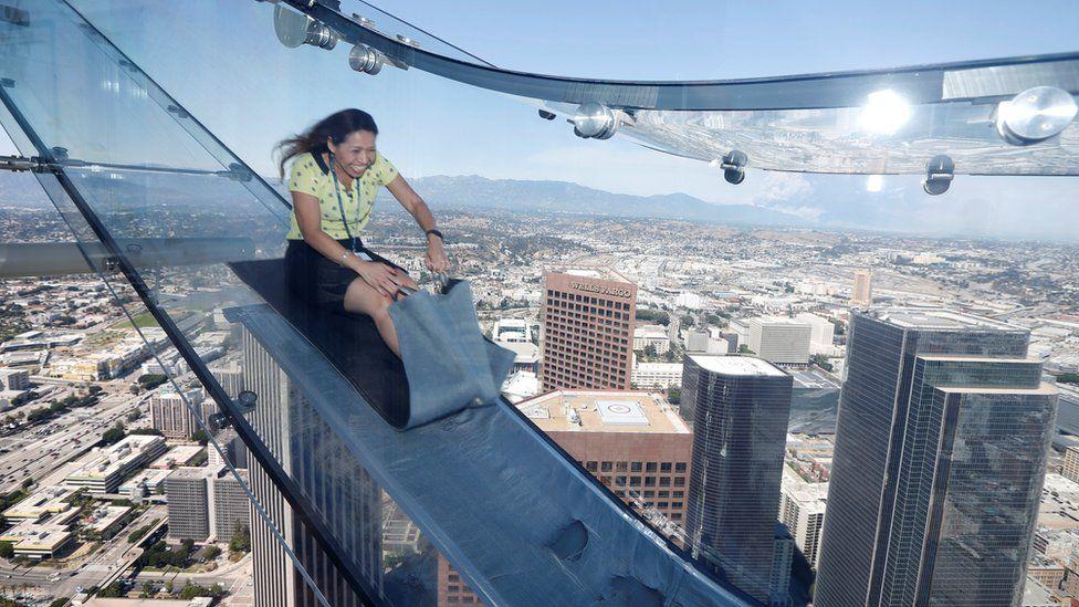A woman rides a glass slide in LA
