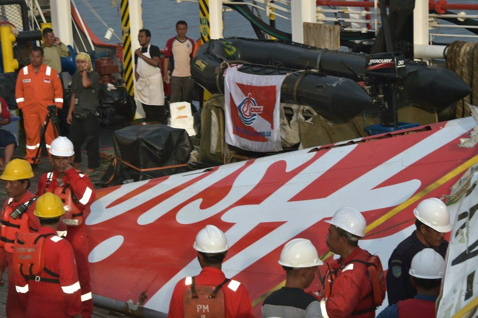 Indonesian crew of the Crest Onyx ship prepare to hoist recovered wreckage of AirAsia flight QZ8501 at port in Kumai on 11 January 2015