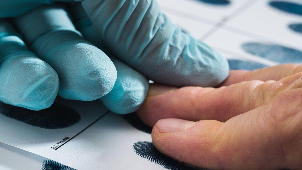 Suspect having fingerprints taken