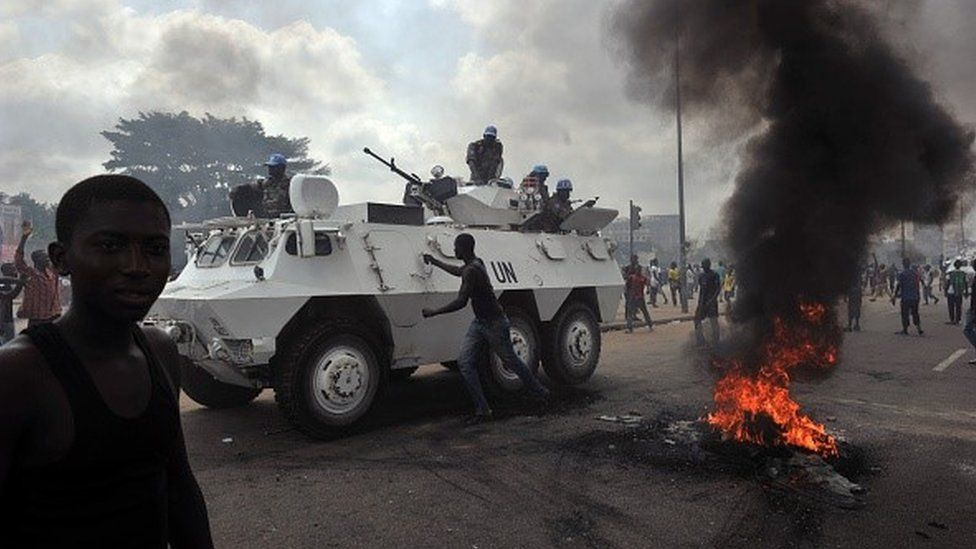 UN peacekeepers drive past supporters of Alassane Ouattara as they demonstrate and burn tyres in the Abobo neighbourhood in Abidjan on February 19, 2011