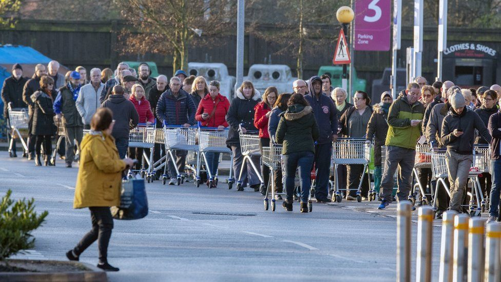 Shoppers queue outside a Tesco supermarket in Liverpool before it opens
