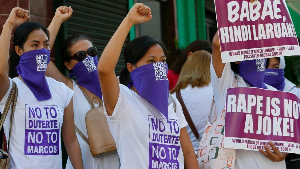 """Female anti-Duterte campaigners stand with fists raised, wearing T-shirts reading """"No to Duterte. No to rape."""""""