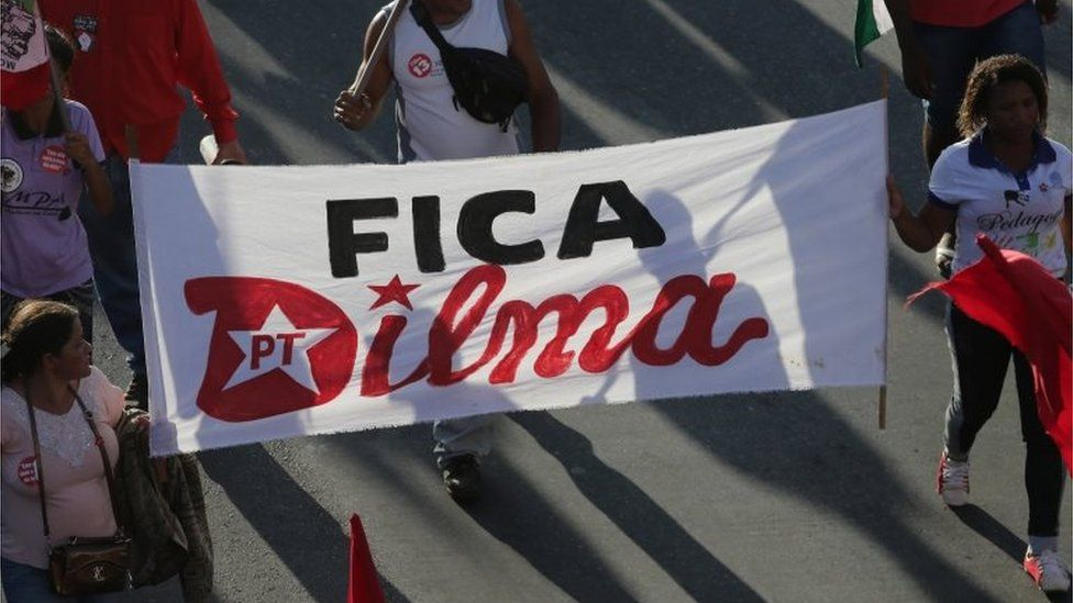 """Government supporters carry a sign that says in Portuguese """"Stay Dilma,"""" as people rally to show their support for Brazil's President Dilma Rousseff and former President Luiz Inacio Lula da Silva in Brasilia, Brazil, Thursday, March 31, 2016"""