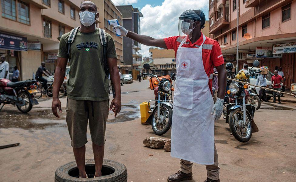 A Red Cross volunteer measures the temperature of a man at Nakasero market in Kampala, Uganda - Wednesday 1 April 2020