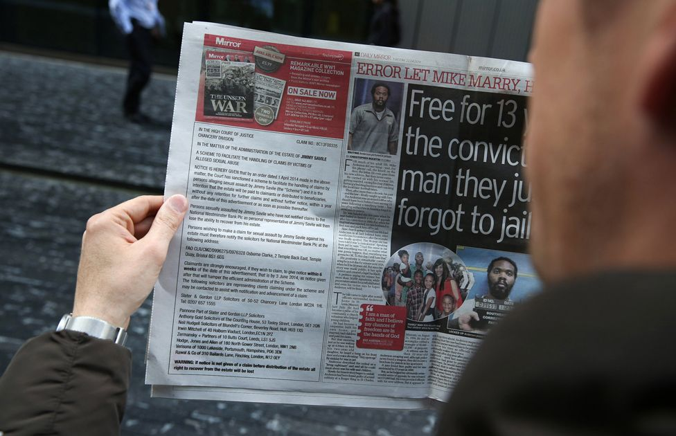 a man holds a newspaper with an advert informing victims how to claim for compensation if they were sexually abused by broadcaster Jimmy Savile on April 22, 2014 in London, England