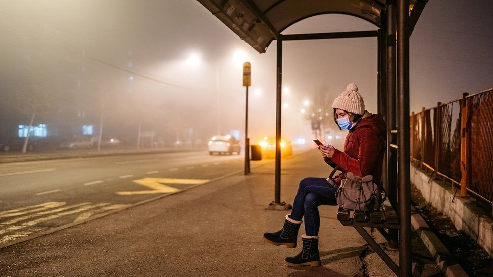 woman wearing mask waits at a bus stop on a foggy night