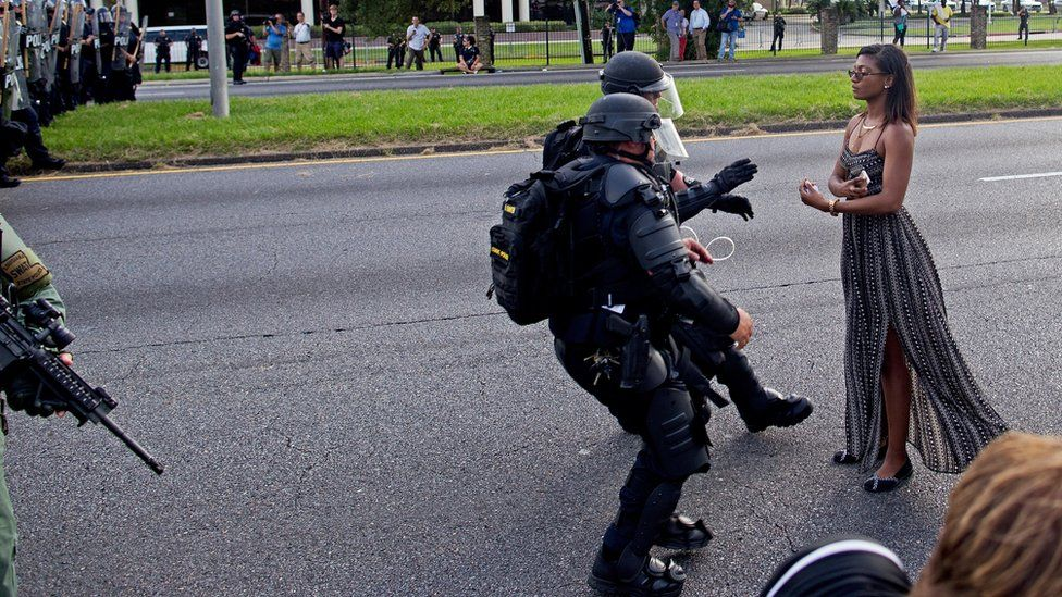 A protester is grabbed by police officers in riot gear after she refused to leave the motor way in front of the the Baton Rouge Police Department Headquarters in Baton Rouge, La., Saturday, July 9, 2016