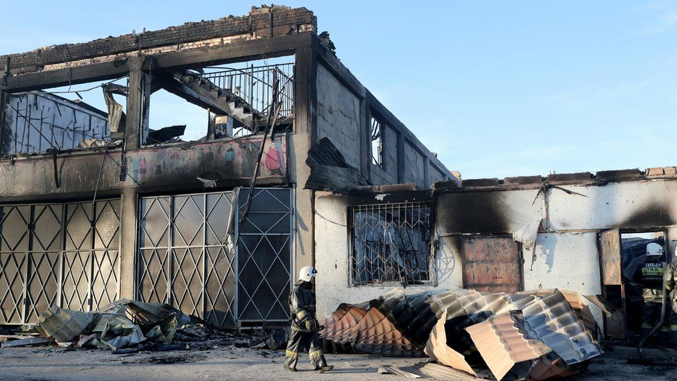 Firefighters douse the remaining fire in burnt houses and property in the village of Blas-Batyr