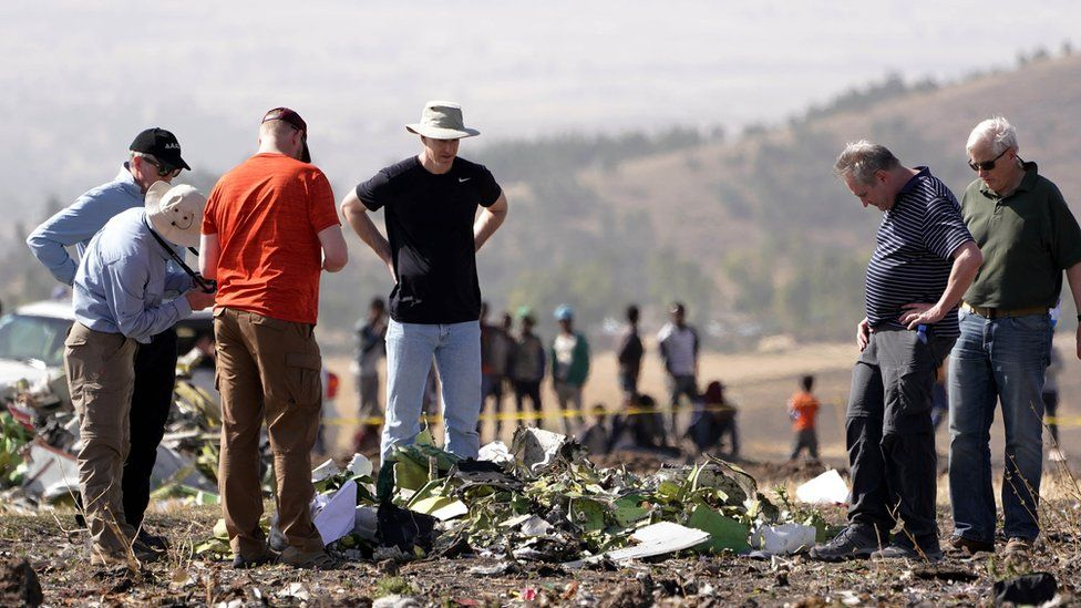 Investigators with the US National Transportation and Safety Board look at debris from the crash site of Ethiopian Airlines Flight ET 302