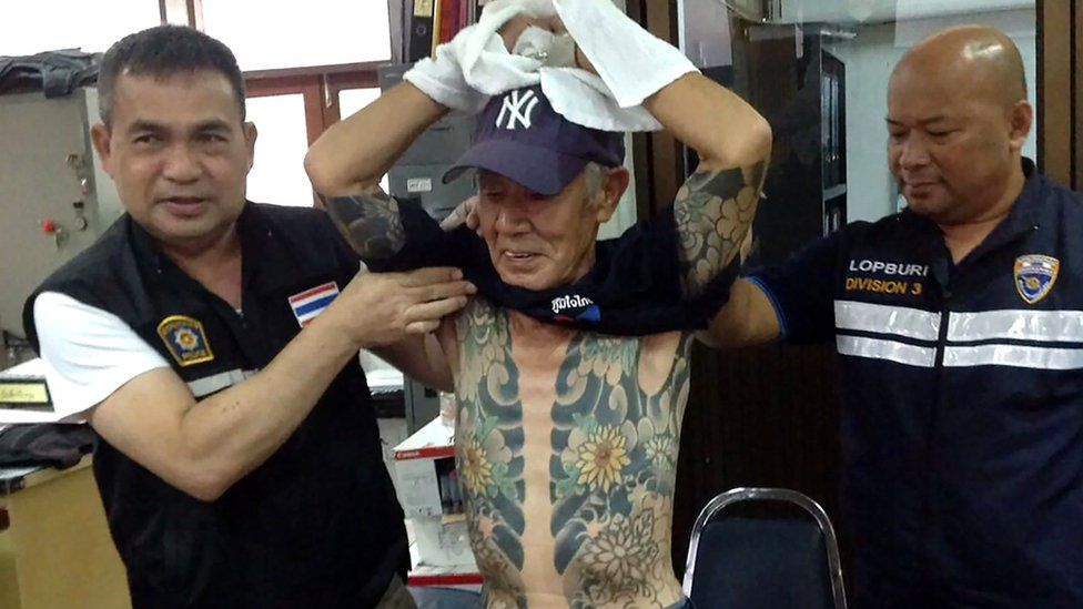 Thai policemen with Mr Shirai, displaying the tattoos on his body