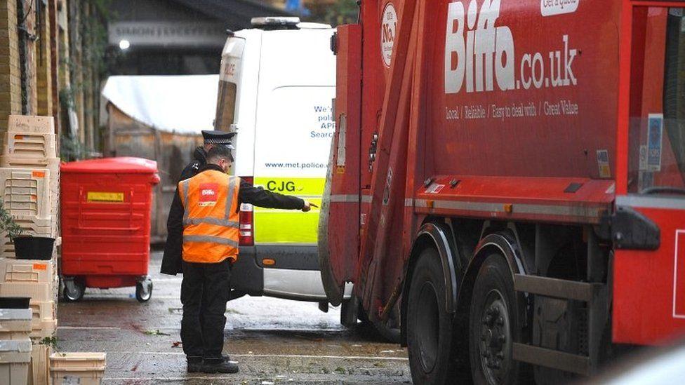 Police officer beside bin lorry