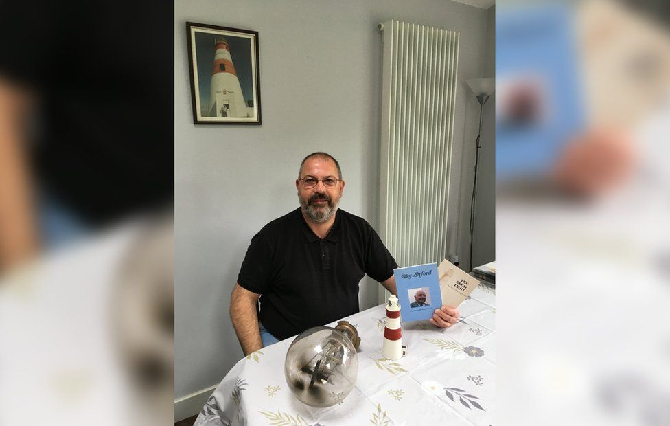 Adrian Underwood with his father's books and a model lighthouse he has at his home in Ireland