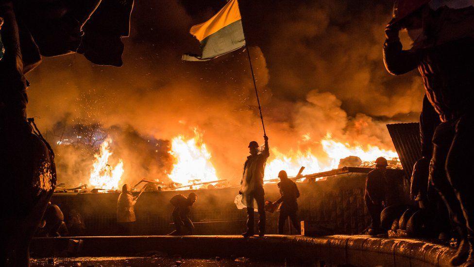 Майдан, палає вогонь, демонстрант із українським прапором