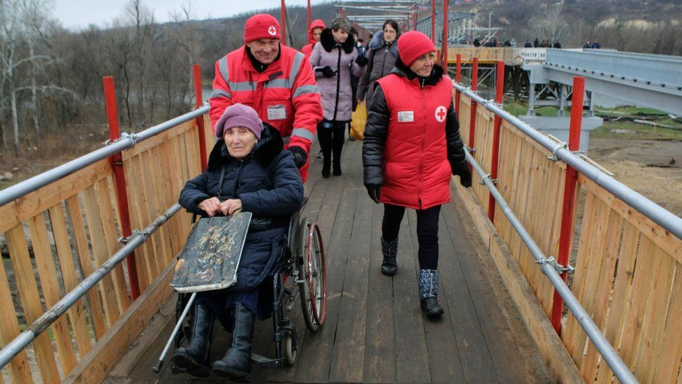 The sick and elderly crossing the bridge in eastern Ukraine, with the help of medics