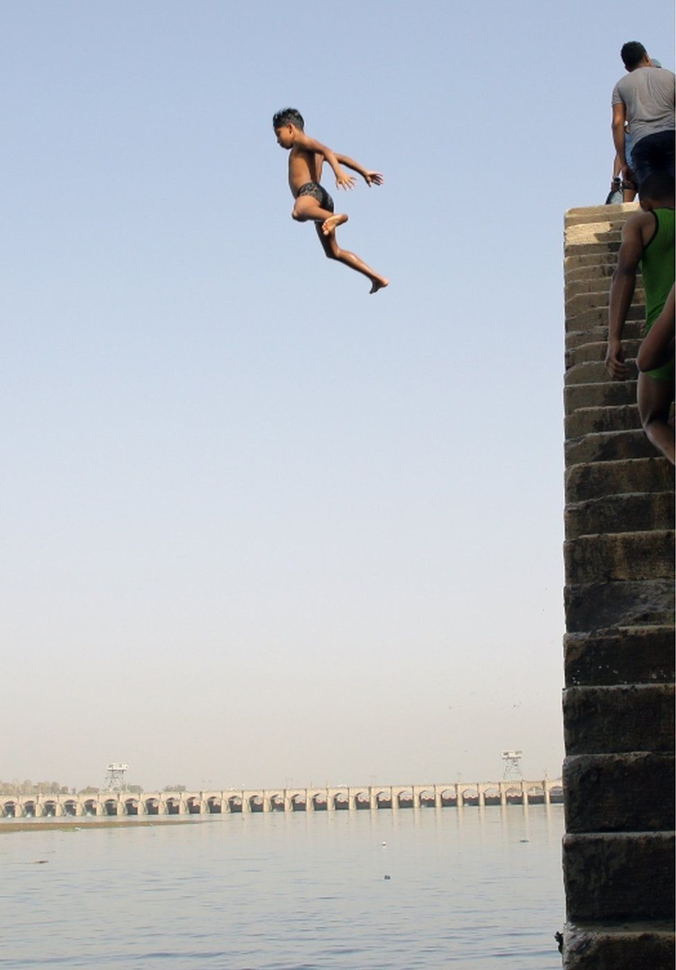 Children jump into the water of the Nile.