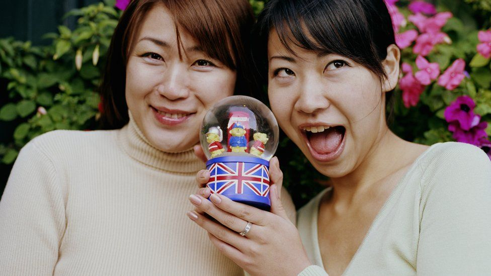 Two women holding a snow globe