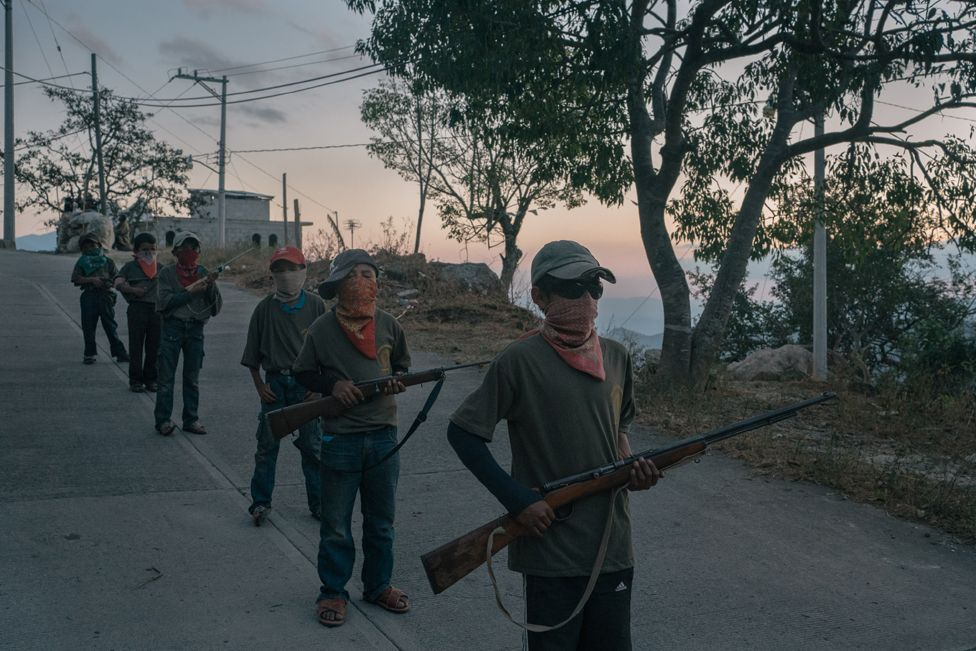 Alex (13), right, and other children stand during a Regional Co-ordinator of Community Authorities community police force gun training presentation in Ayahualtempa, Guerrero state, Mexico.