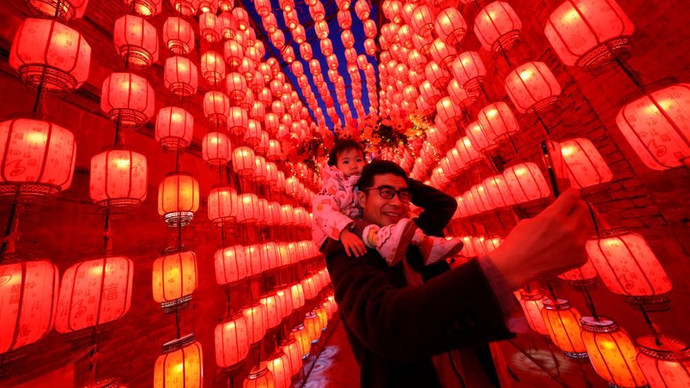 A man takes a picture of himself and a child during the Lantern Festival in Taiyuan, northern China. Photo: 26 February 2021
