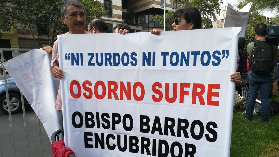 """Protesters hold up a sign reading """"Neither lefties nor stupid, Osorno is suffering, Bishop Barros [guilty of] cover-up"""