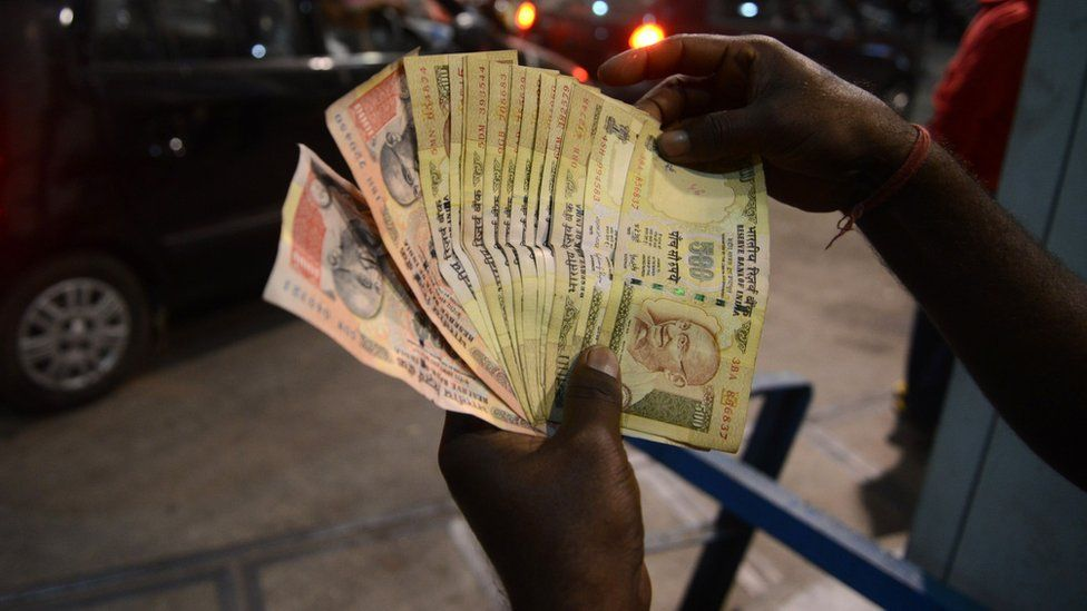 An Indian fuel station employee checks a 500 and 1000 rupee notes as residents queue up at a fuel station in Siliguri on November 8, 2016.