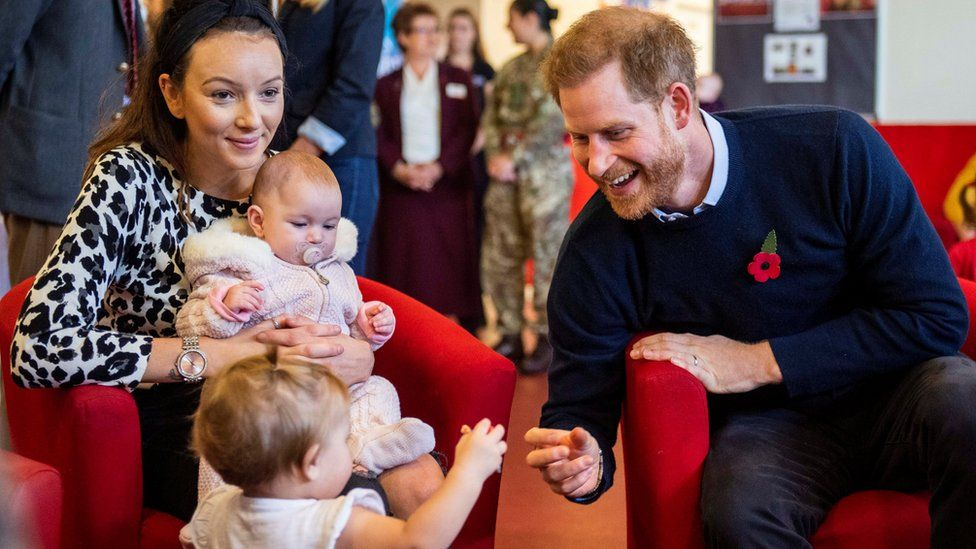 Prince Harry smiles at a toddler at Windsor's Broom Farm Community Centre
