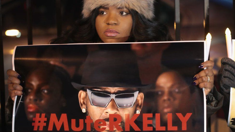 A protester holding a #MuteRKelly sign