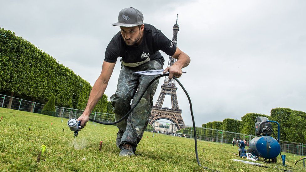 French artist Saype works on a monumental fresco on the Champ-de-Mars in Paris, France