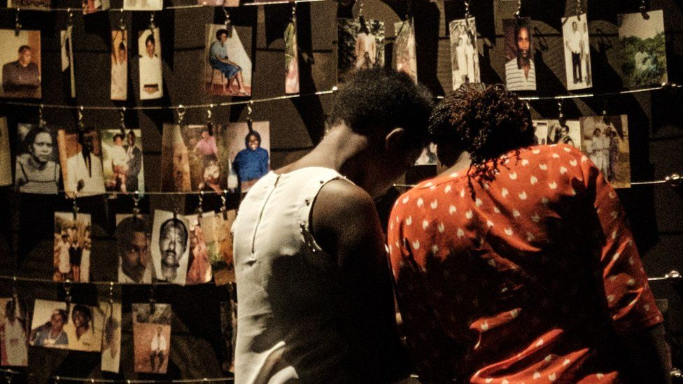 A picture taken on April 29, 2018 shows a visitors looking at victims' portraits at the Kigali Genocide Memorial in Kigali, Rwand