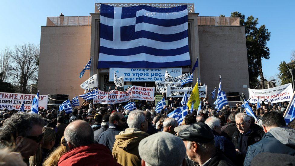 A giant Greek flag hangs on the municipal theatre of the city of Mytilene as locals take part in a protest against overcrowded migrants camps on the island of Lesbos, Greece, January 22, 2020