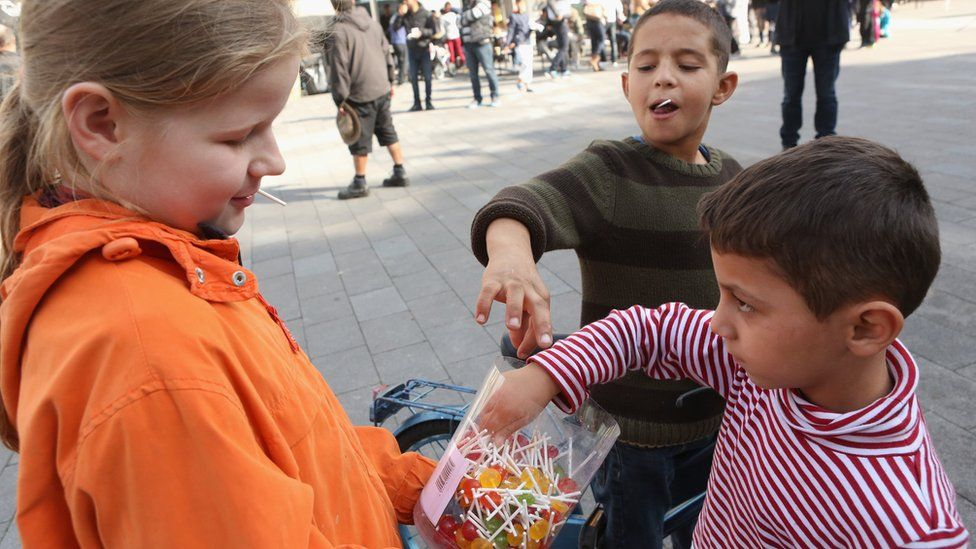 Lea, 12 (L), gives lollipops to Syrian refugee children at a welcome festival (Willkommensfest) for migrants on September 19, 2015 in the Karolinenviertel neighborhood of Hamburg, Germany