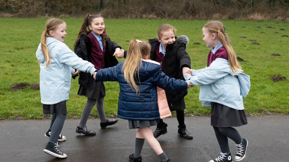 A group of children play outdoors at Glan-Yr-Afon primary school in Cardiff