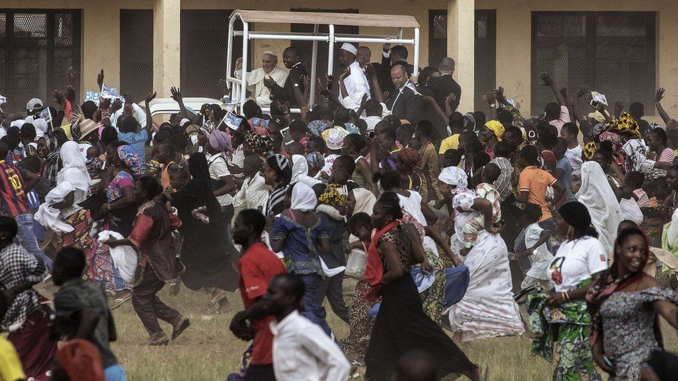 Crowds run after Pope Francis as he waves, during a visit to the Koudoukou school, Bangui