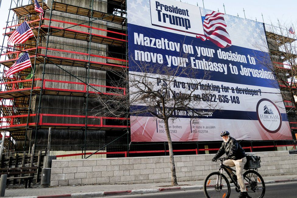 Man cycles past banner on a building in Jerusalem welcoming Donald Trump's plan to move the US embassy to Tel Aviv