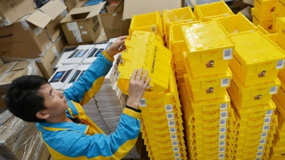 An employee piles up reusable boxes to be used ahead of the Singles Day online shopping festival in Nanjing, Jiangsu province, China (28 October 2017)