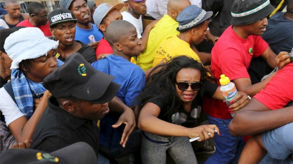 Student reacts during their confrontation with security guards as they protest over planned increases in tuition fees outside the University of Johannesburg