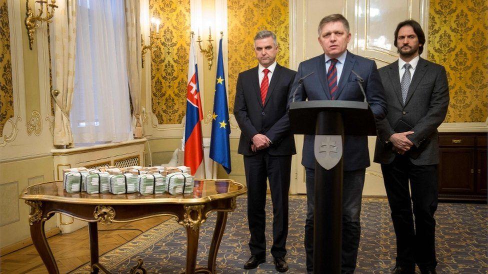 Slovak Prime Minister Robert Fico (C) is flanked by Slovak Police President Tibor Gaspar (L) and Slovak Interior Minister Robert Kalinak (R) next to bundles of euro banknotes